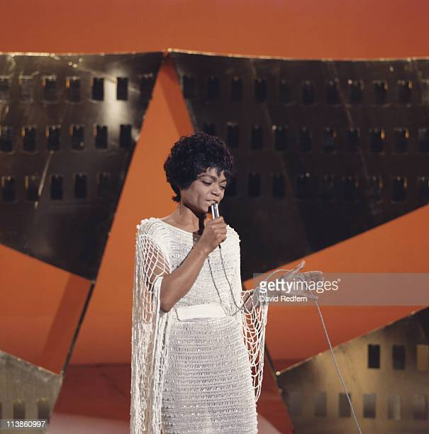 Eartha Kitt US singer and actress singing into a microphone during a live concert performance circa 1970