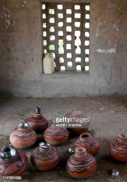 Earthen pots filled with water are kept in the shade on a roadside during a hot day on the outskirts of Churu in Rajasthan on June 4 2019...