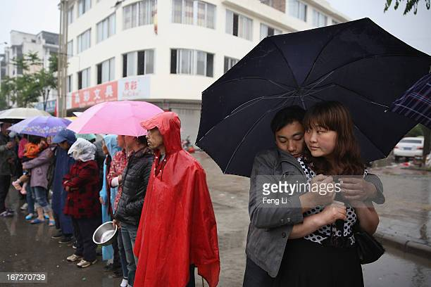 Earthquake survivors queue for free food in the rain on April 23 2013 in Lushan of Ya An China A magnitude 7 earthquake hit China's Sichuan province...
