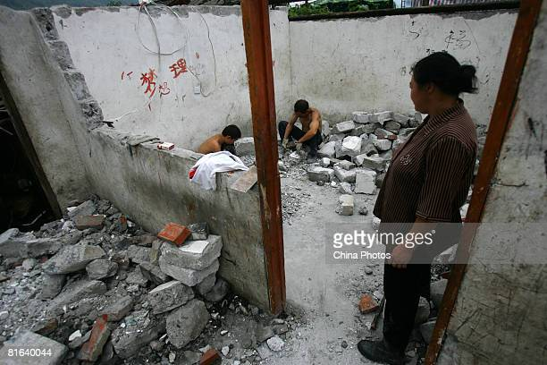 Earthquake survivors select bricks to re-build their house in their destroyed home at the Yinghua Township on June 19, 2008 in Shifang of Sichuan...