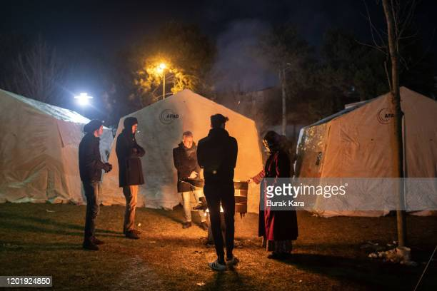 Earthquake survivors spend the night as they warm around a fire near a makeshift tent in a park on January 25 2020 in Elazig Turkey The 68magnitude...