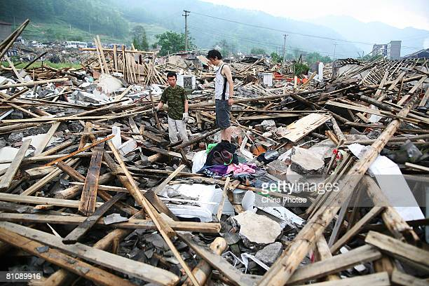 Earthquake survivors try to salvage what they can from their destroyed houses in the Ronghua Township on May 14, 2008 in the outskirts of Shifang,...