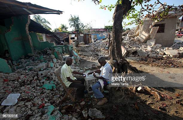 Earthquake survivors Vilgan Saint Louis and Joreste Cossi whose wife died in the earthquake play dominoes February 15 2010 in Leogane Haiti Leogane...