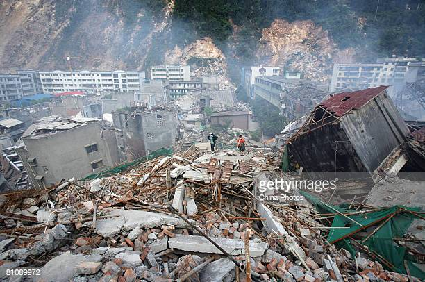 Earthquake survivors walk on the debris of collapsed houses, in search of relatives on May 14, 2008 in Beichuan County, Sichuan Province, China. A...