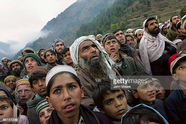 Earthquake survors watch as a UN helicopter carrying food aid arrives on November 11 2005 in Rashang in the high Alai Valley of Pakistan In recent...