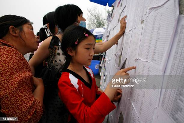 Earthquake victims look at a missing persons list trying to find a family member at a stadium that has become a massive refugee camp May 20 2008 in...