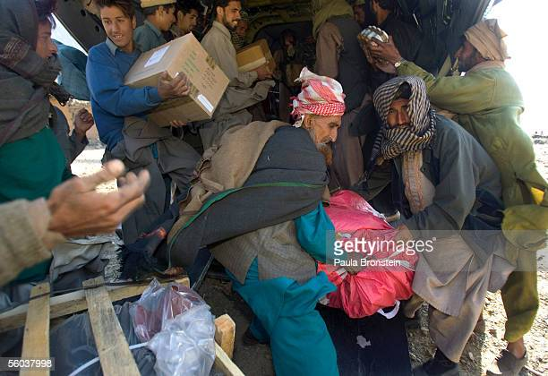 Earthquake victims scramble to unload food relief aid from a US Army Chinook helicopter October 31 2005 in Gantar village in the remote Alai valley...