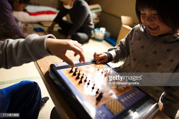 Earthquake victims spend time with chess game at an evacuation shelter on April 3 2011 in Otsuchi Iwate Prefecture Japan The 90 magnitude strong...