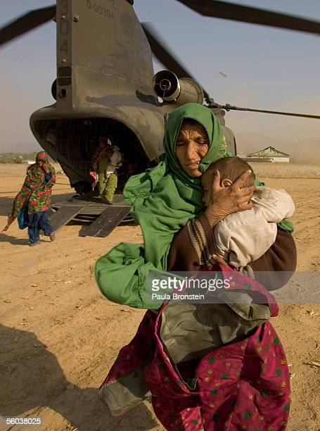 Earthquake victims that were among 40 people transported by a US Army Chinook helicopter from the devastated and remote village of Gantar arrive at a...