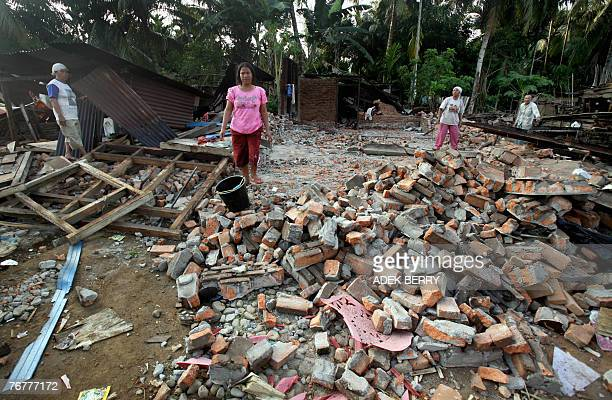 Earthquake-affected victims walk amongst their collapsed homes in Lubuk Pinang, Muko Muko, 16 September 2007. The death toll from a series of major...