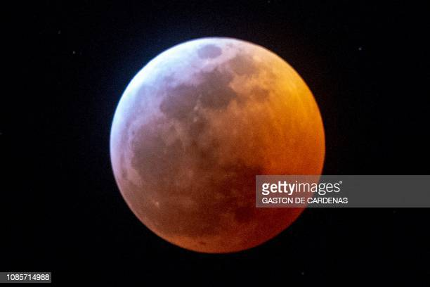 TOPSHOT Earth's shadow almost totally obscures the view of the socalled Super Blood Wolf Moon during a total lunar eclipse on Sunday January 20 in...