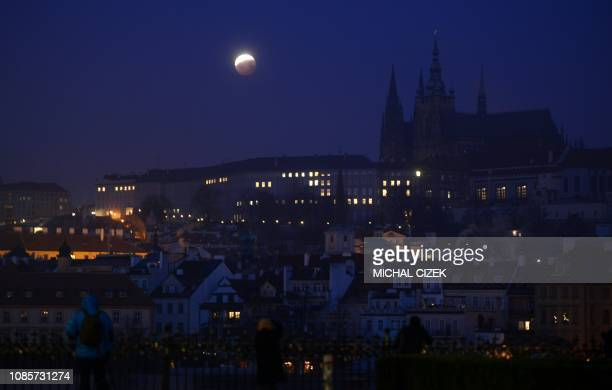 Earth's shadow moves across the Super Blood Wolf Moon over the Prague Castle during a lunar eclipse on January 21 2019 in the Czech capital Prague