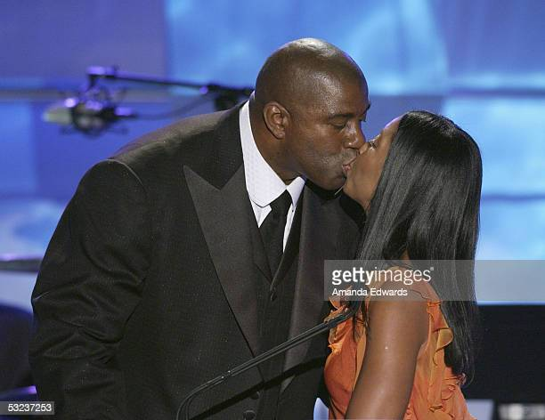 Earvin Magic Johnson kisses his wife Cookie on stage during the 20th Annual Midsummer Night's Magic Awards Dinner on July 13 2005 at the Century...