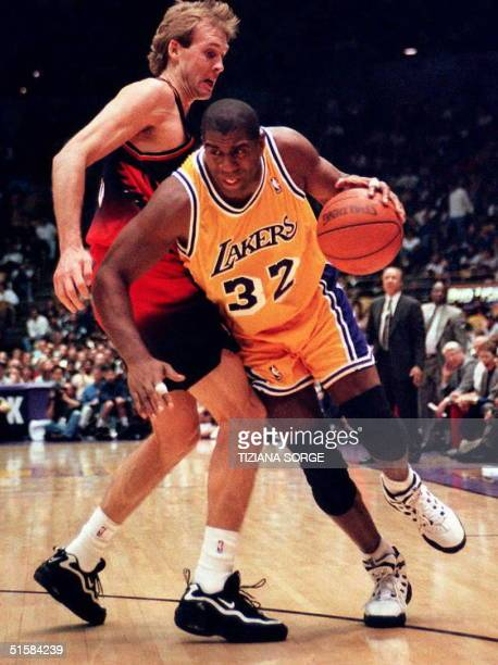 Earvin Magic Johnson of the Los Angeles Lakers drives against foward Craig Ehlo of the Atlanta Hawks 14 February in Inglewood California The Lakers...