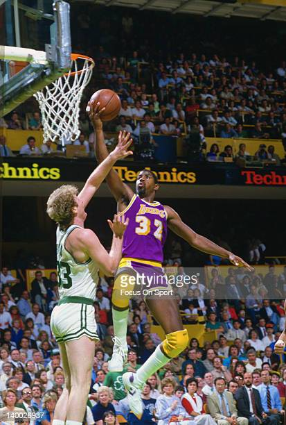Earvin Magic Johnson of the Los Angeles Lakers goes up to shoot over Larry Bird of the Boston Celtics during the 1985 NBA Basketball Finals at the...
