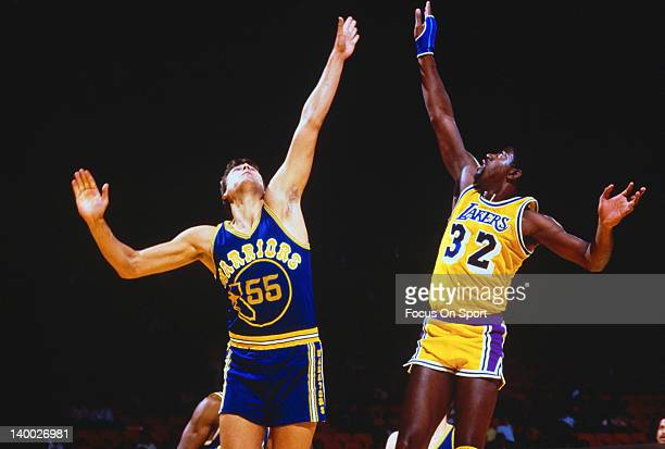 Earvin Magic Johnson of the Los Angeles Lakers leaps for the ball with Chris Engler of the Golden State Warriors during an NBA basketball game circa...