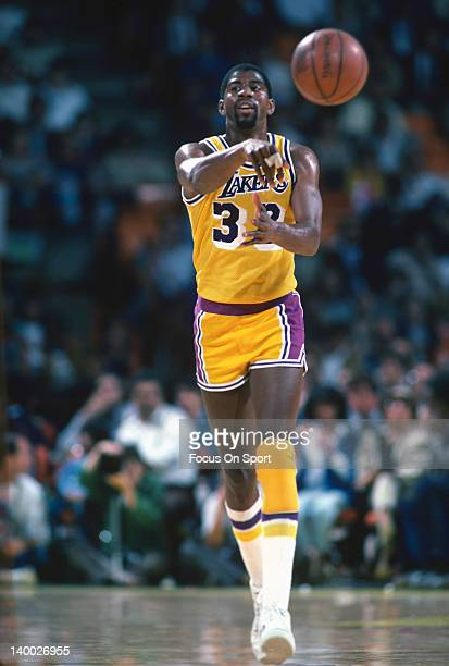 Earvin Magic Johnson of the Los Angeles Lakers passes the ball up court during an NBA basketball game circa 1983 at The Forum in Inglewood California...
