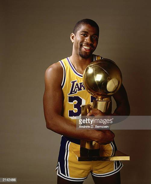 Earvin Magic Johnson of the Los Angeles Lakers poses for a portrait with the NBA Championship trophy in 1985 in Inglewood California NOTE TO USER...