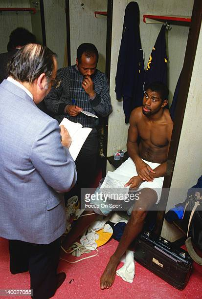 Earvin Magic Johnson of the Los Angeles Lakers sits in the locker room talking with the media after an NBA basketball game circa 1983 at The Forum in...
