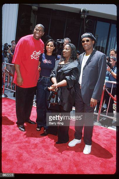 Earvin Magic Johnson poses at the premiere of The Phantom Menace with his wife daughter and friend Samuel L Jackson May 16 1999 in Los Angeles CA...