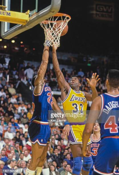 """Earvin """"Magic"""" Johnson, Shooting Guard and Power Forward for the Los Angeles Lakers jumps to make a lay up shot to the basket as Larry Nance of the..."""