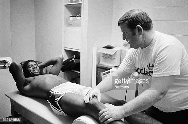Earvin Magic Johnson the prize rookie of the Los Angeles Lakers injured when he fell in a game against Seattle 10/17 has his knee treated by Laker...