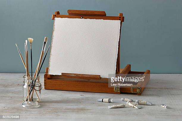 Easel with blank sheet of watercolor paper, paintbrushes, and tubes of paint