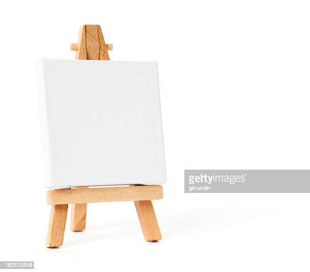 Easel with blank white canvas on white background