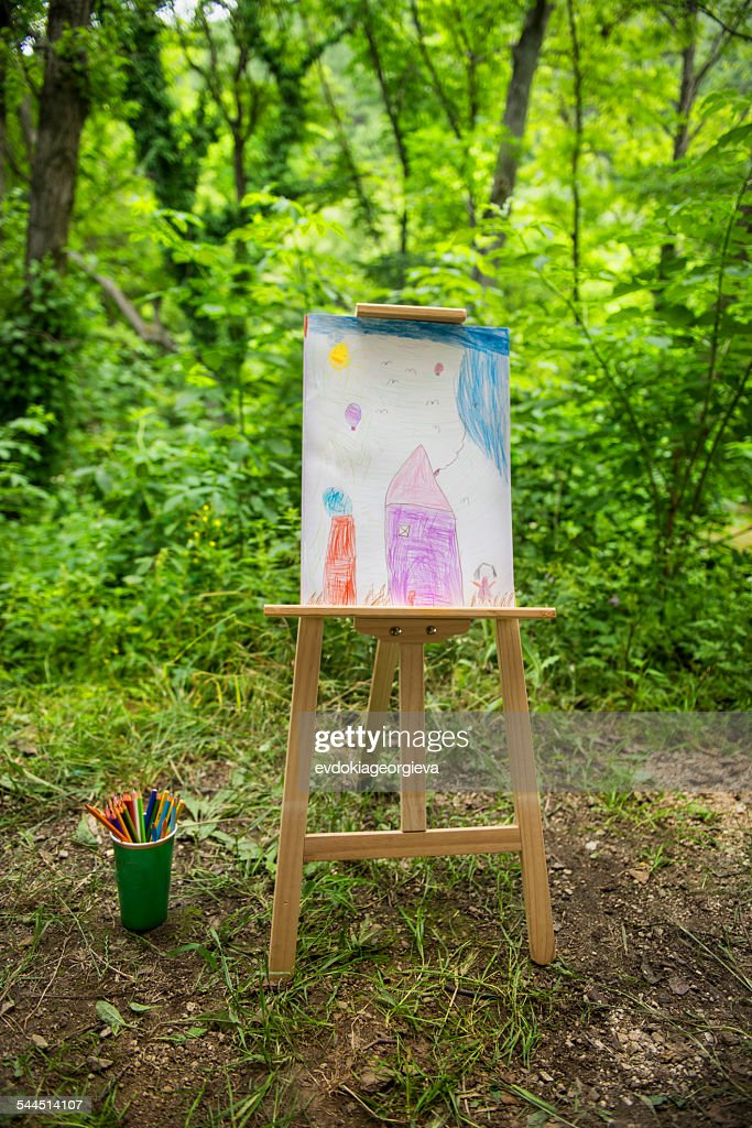 Easel with child's drawing in forest : Stock Photo