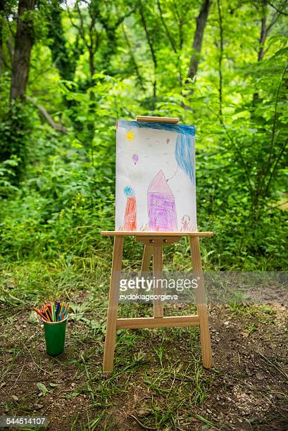 Easel with child's drawing in forest