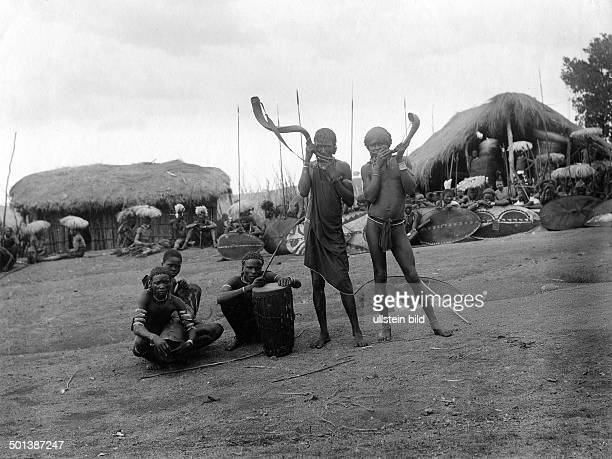 East Africa ethnic group of the Massai Musicians and Massai warriors in a village probably in the 1910s