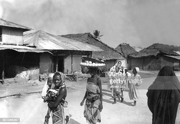 Native woman carries a dish with cheese on her head probably in the 1910s