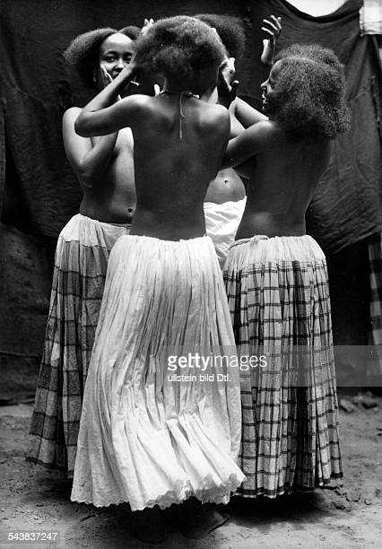 East Africa Somalia Young seminacked women dressed in long skirts dancing together um 1940 Photographer Hugo Adolf BernatzikVintage property of...