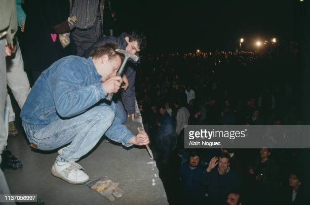 East and West Germans tear down the Berlin Wall on November 9, 1989. Berlin had been politically divided since the end of World War II, with the...