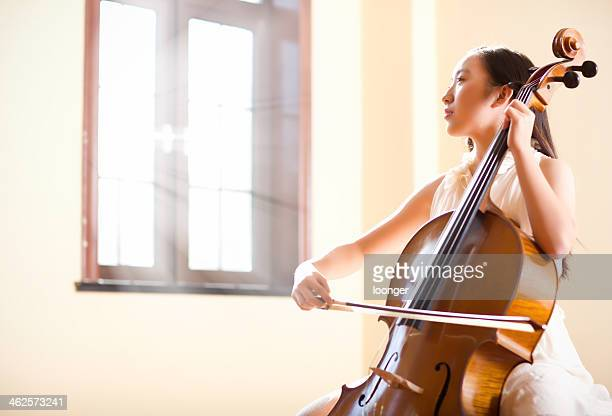 East asian teenage girl playing cello