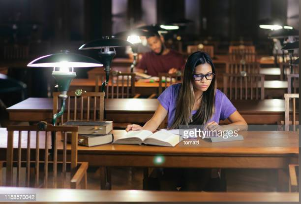east asian woman reading in library - library stock pictures, royalty-free photos & images