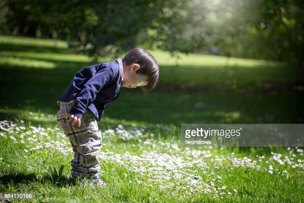 East asian young boy exploring in a public park.