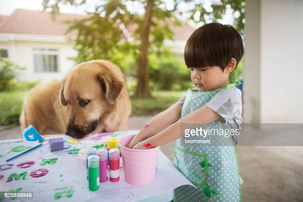 East asian young boy in art painting session with pet dog.