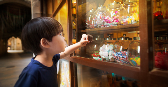 East asian young boy looking at colourful candy jars. - gettyimageskorea