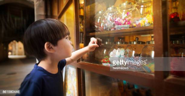 east asian young boy looking at colourful candy jars. - china east asia stock pictures, royalty-free photos & images