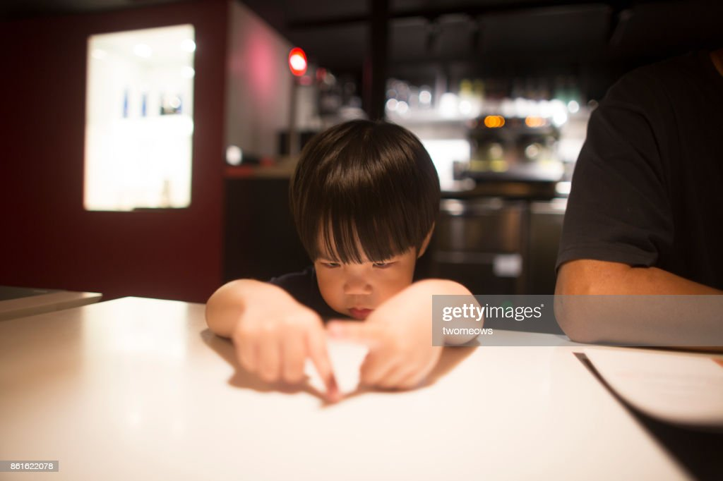 East asian young boy looking bored by waiting time in restaurant. : Stock Photo