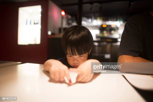 east asian young boy looking bored by waiting time in restaurant. - china east asia stock photos and pictures