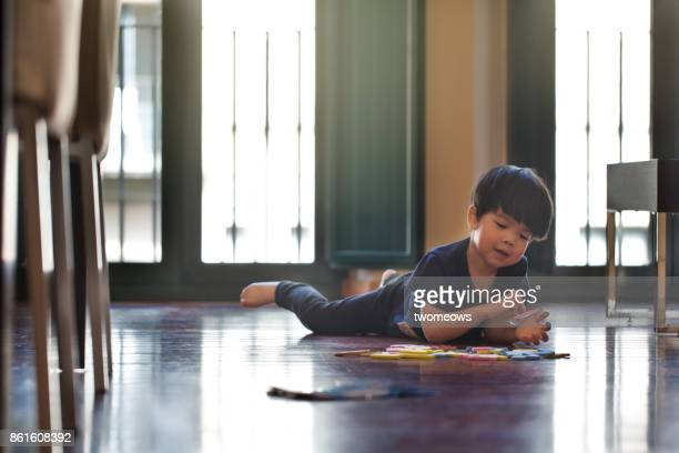 east asian young boy playing puzzle on wooden floor. - china east asia foto e immagini stock