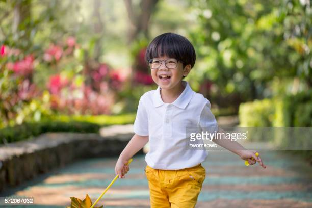 East asian young boy playing toy windmill in garden.