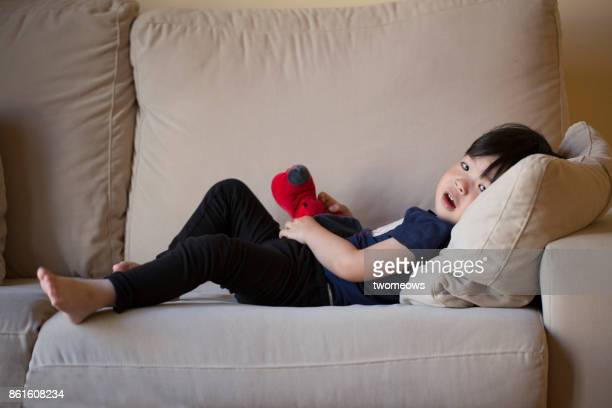 East asian young boy relax on sofa.