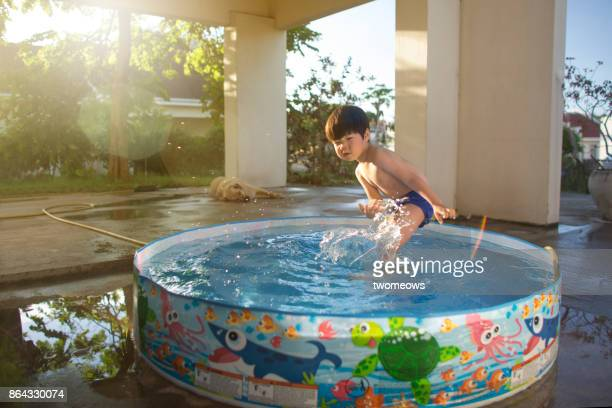 east asian young boy water play during summer time. - china east asia stock pictures, royalty-free photos & images