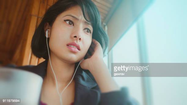 East Asian young woman listening podcast.
