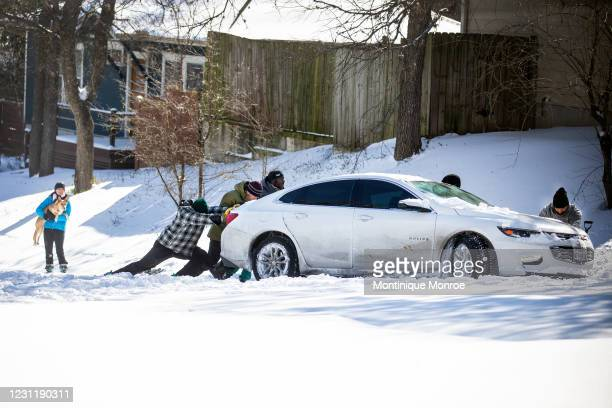 East Austin residents push a car out of the snow on February 15, 2021 in Austin, Texas. Winter storm Uri has brought historic cold weather to Texas,...
