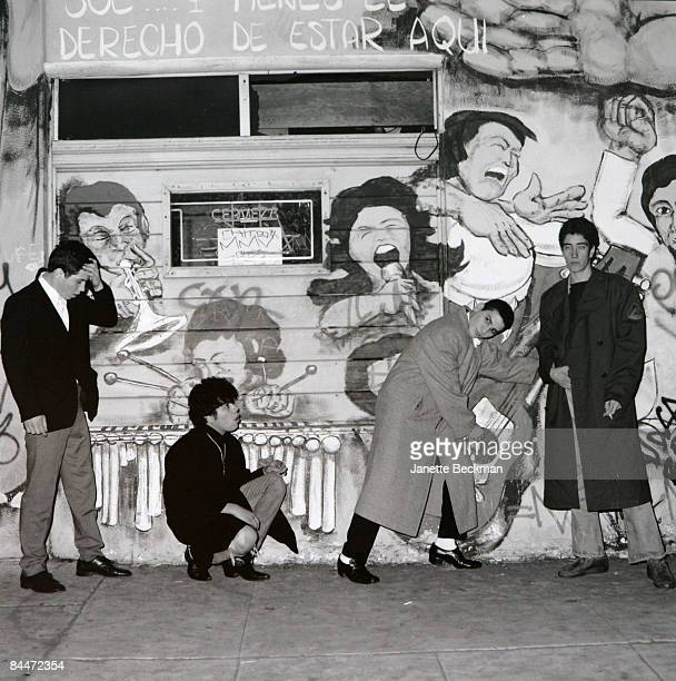 East LA band Undertakers posing for a portrait against a wall with a mural on it Los Angeles 1983