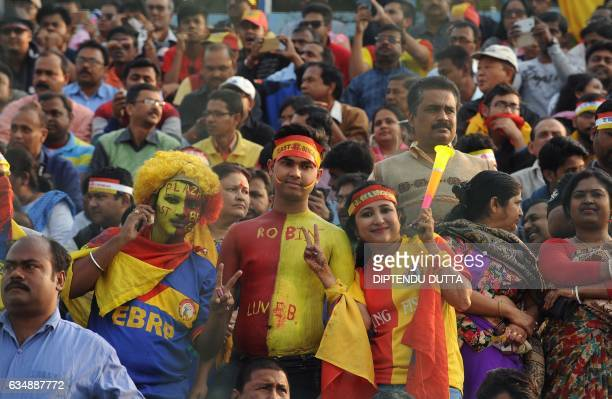 East Bengal supporters cheer their team during an Indian I-League football match between Mohun Bagan and East Bengal at the Kanchenjungha Stadium in...